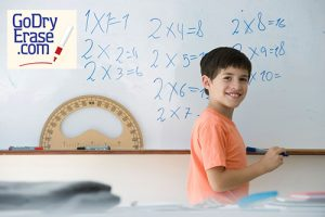 BENGDD Elementary school student writing equations on whiteboard, smiling over shoulder at camera